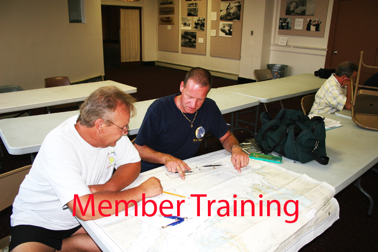 A Photo of Auxiliary members looking at a ocean chart.