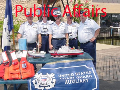 A Photo of Auxiliary members standing in formation behind a table that has boating saftey information flyers on it.